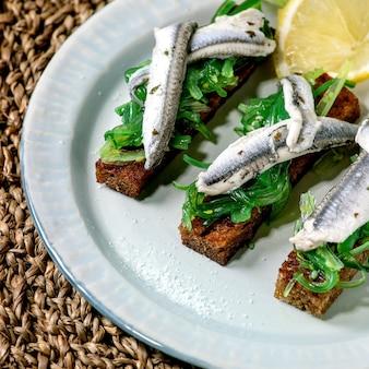 Закуски тапас маринованные анчоусы или филе сардин салат из водорослей вакаме на поджаренном ржаном хлебе, подается на синей тарелке с лимоном на соломенной салфетке в качестве фона.