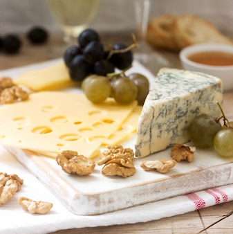 Appetizers of various types of cheese, grapes, nuts and honey, served with white and red wine
