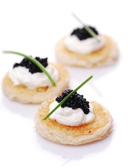 Appetizers with caviar on white