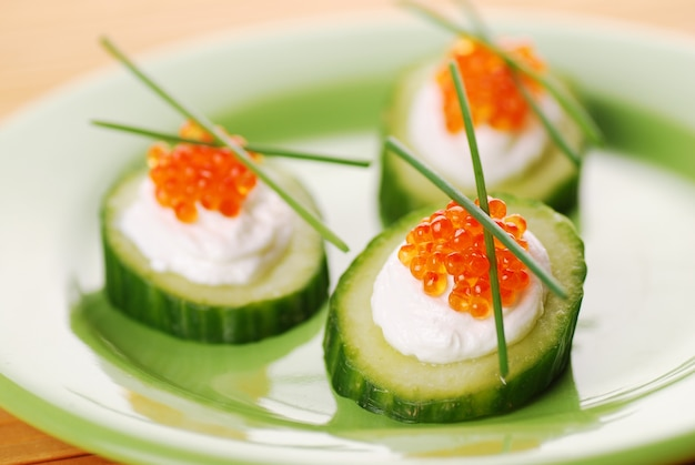 Appetizers with red caviar and a cucumbe
