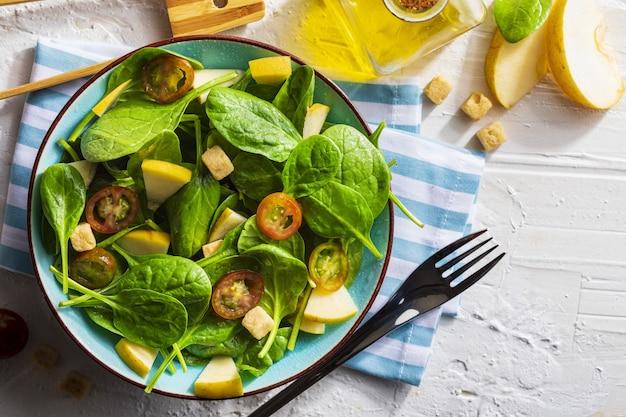 Аппетитный и полезный низкокалорийный вегетарианский салат со ростками шпината, свежим яблоком, помидорами и тостами.