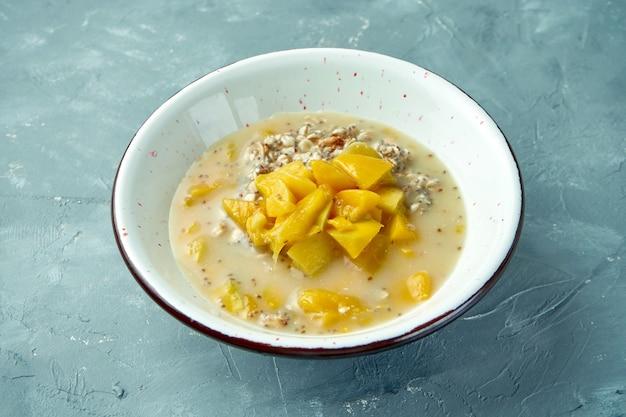 白いボウルにマンゴーとチアの食欲をそそる健康的なオートミール