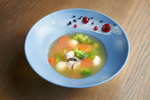食欲をそそる健康的なシーフードスープ、ブロッコリー、ニンジン、モッツァレラチーズ、カキ、木製の表面にある青いセラミックボウル。投稿中のフィルム効果。ソフトフォーカス