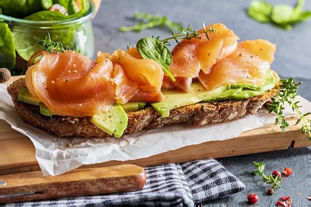 Аппетитный и полезный копченый лосось с авокадо и овощами (ростки шпината, помидоры, тимьян) на тосте. самодельный вид.
