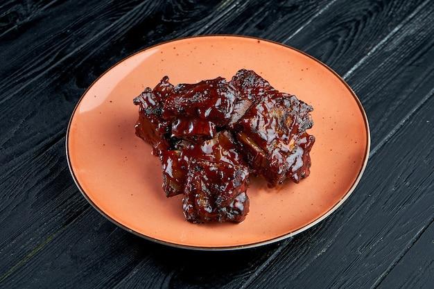 바비큐 소스에 식욕을 돋우고 육즙이 많은 쇠고기 갈비는 어두운 배경에 접시에 제공됩니다.