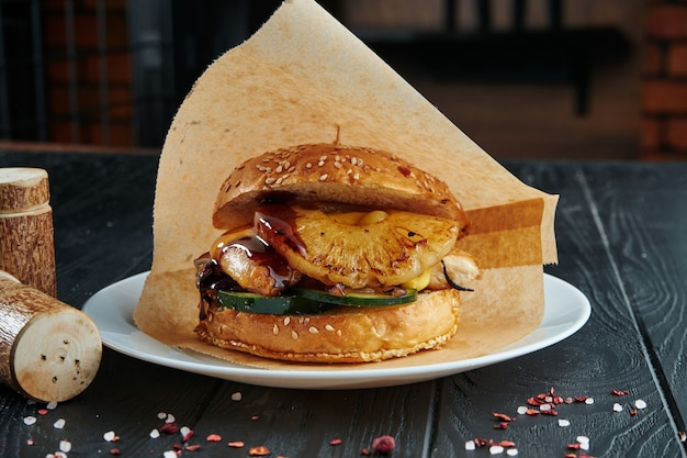 食欲をそそるジューシーなハンバーガーとパイナップルのグリル、ズッキーニ、玉ねぎ、チキンカツレツとフライドポテトの白い皿の上。閉じる