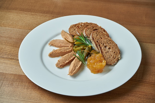 Appetizing antipasti - goose paste with jam, rosemary and rye bread in white plate on wooden table/