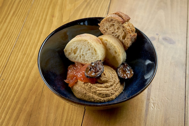 Appetizing appetizer - chicken pate with quince and dried baguette in a bowl on a wooden background