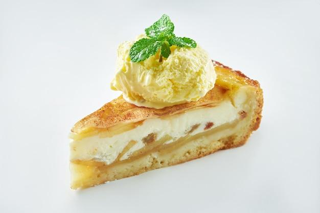 Аппетитный пудинг яблочного пирога с ванильным мороженым, изолированным на белом столе. крупным планом, выборочный фокус