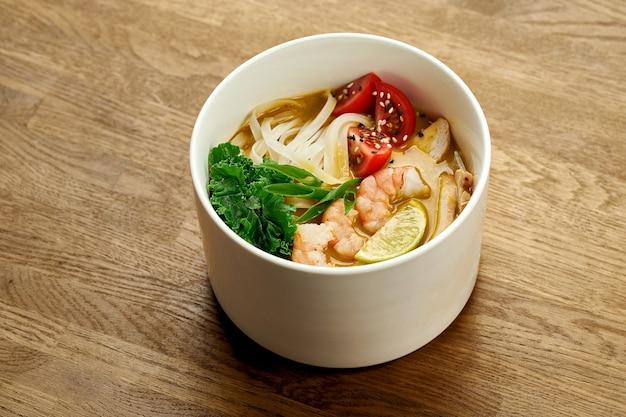 나무 배경에 있는 흰색 그릇에 새우와 라임이 있는 코코넛 우유에 식욕을 돋우는 아시아 카레 락사 수프