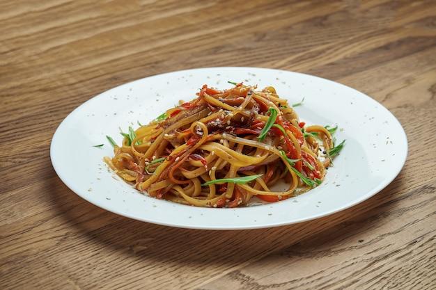 ピーマン、玉ねぎ、にんじん、アヒルの木製の背景の白いプレートに食欲をそそるアジアの中華麺。