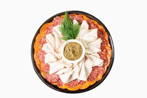 Аппетитный ассортимент разнообразных копченых колбас с соусом на тарелке. вид сверху. изолированный над белизной.