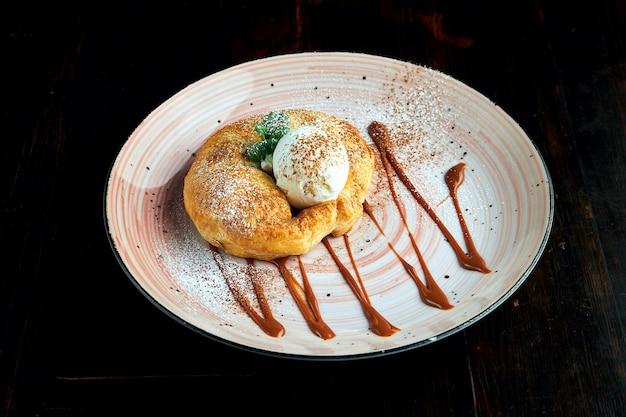 食欲をそそるオーストリアのペストリーデザート-甘いソースと白いアイスクリームを添えたアップルシュトルーデル、暗い表面に対してプレートで提供