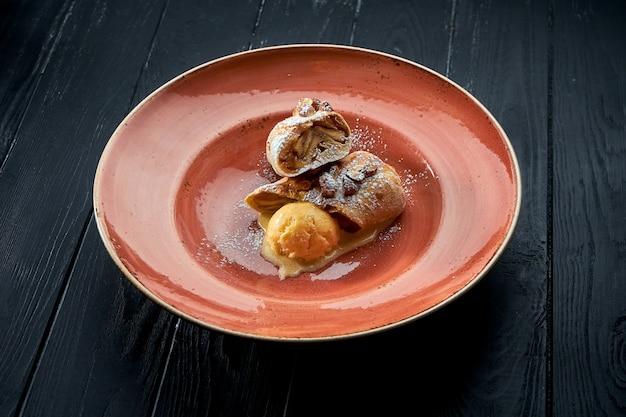 食欲をそそるオーストリアのペストリーデザート-甘いソースと黄色いアイスクリームを添えたアップルシュトルーデル、暗い表面に対してプレートで提供