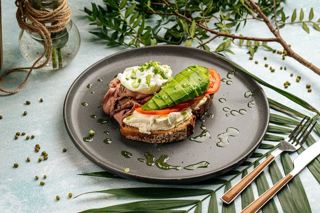 Appetizing avocado sandwich with roast beef and poached egg for breakfast