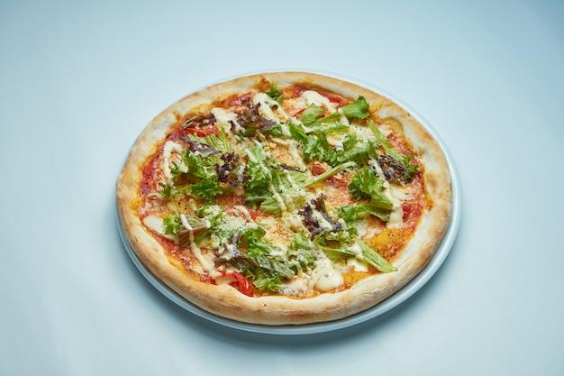 グレーの表面に白い皿にクリームソース、レタス、チキン、パルメザンチーズの食欲をそそる焼きたてのイタリアのピザ。ピザシーザー