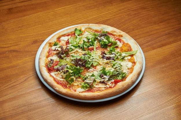 木製のテーブルの上の白い皿にクリームソース、レタス、チキン、パルメザンチーズの食欲をそそる焼きたてのイタリアのピザ。ピザシーザー