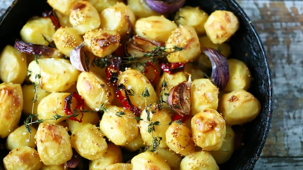 Appetizing baked potatoes whole in a pan. rustic baked potato with garlic, herbs and spices.