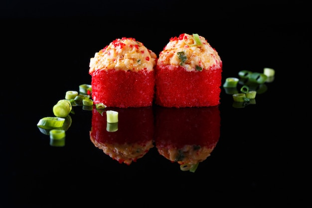 Appetizing baked sushi roll with fish, green onions on a black background with reflection menu and restaurant