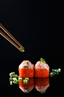 Appetizing baked sushi roll with fish, green onions with chopsticks on black