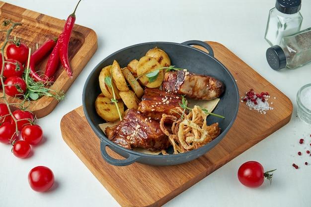 木製トレイのフライドポテトと蜂蜜ソースで食欲をそそるバーベキュー豚カルビ。食品の組成物。閉じる