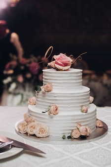 Appetizing beautiful big layered sweet wedding cake covered by white cream decorated dessert flower