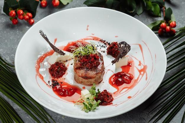 甘いソースで食欲をそそる牛肉をクローズアップ。牛肉のみじん切りをチェリーソースで野菜を盛り付けたもの。おいしいヨーロッパ料理。