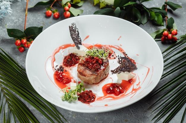 甘いソースで食欲をそそる牛肉をチェリーソースで刻んだ牛肉を皿に野菜と一緒にクローズアップ