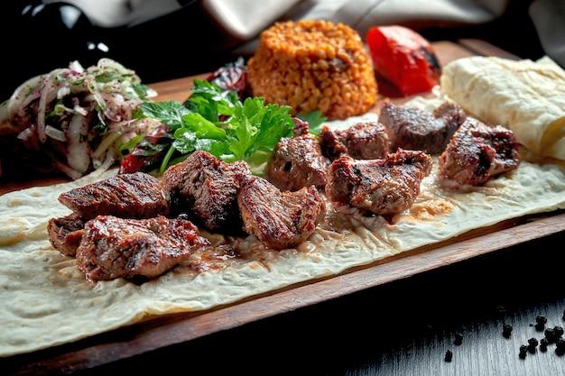 구운 야채, 불구 르, 절인 양파를 곁들인 식욕을 돋우는 쇠고기 케밥