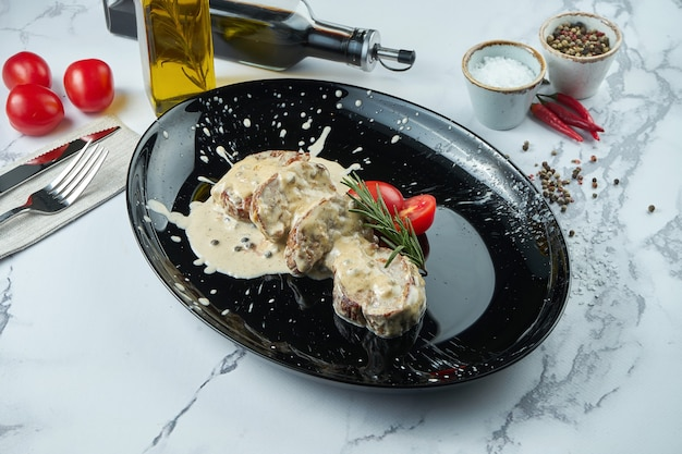 Appetizing beef pepper steak with mushroom sauce, served in a black plate on a marble surface