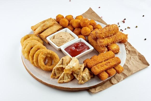 식욕을 돋우는 맥주 스낵-튀긴 스낵, 모짜렐라, 양파 링, 피시 스틱, 감자 크로켓과 소스 및 나무 보드 세트. 흰색 표면