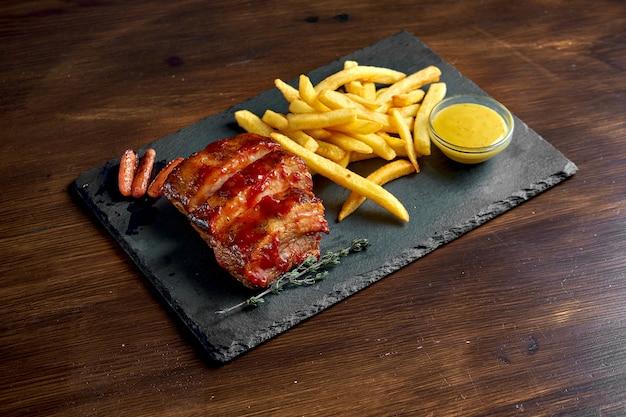 식욕을 돋우는 맥주 스낵-블랙 플레이트에 제공되는 허니 소스와 감자 튀김의 bbq 돼지 갈비