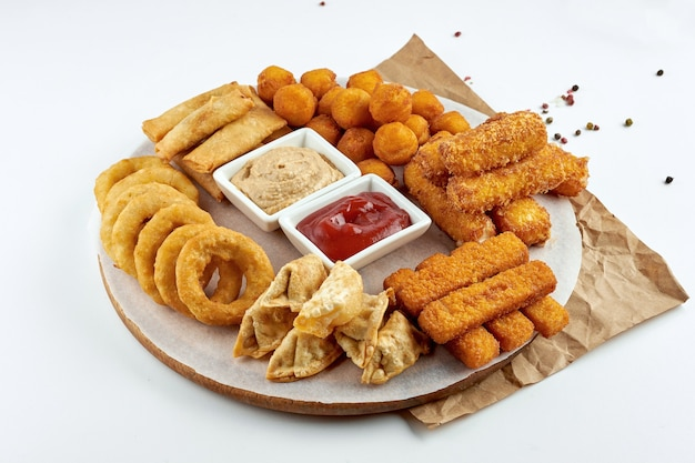 Appetizing beer snack - a set of deep-fried snacks, mozzarella, onion rings, fish sticks, potato croquettes with sauce and on a wooden board. white surface
