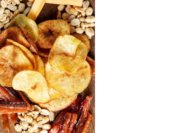 접시에 식욕을 돋 우는 맥주 스낵. 튀긴 소시지, 칩, 소금에 절인 견과류, 훈제 치즈. 흰색 배경에 고립. 텍스트를 위한 공간입니다.