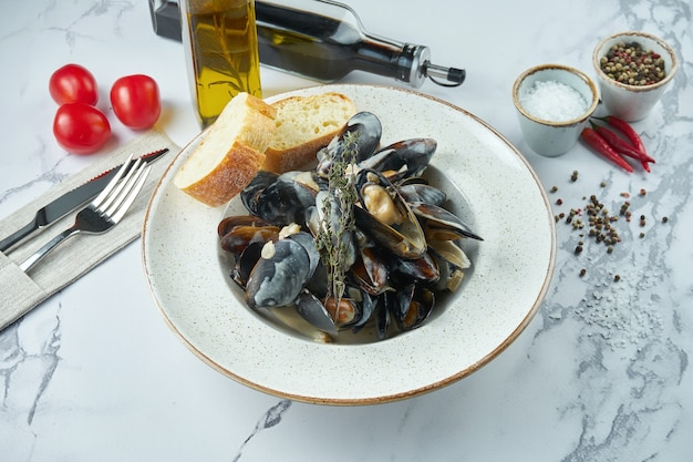 Appetizing boiled chilean mussels in a creamy garlic sauce with croutons in a white plate on a marble surface
