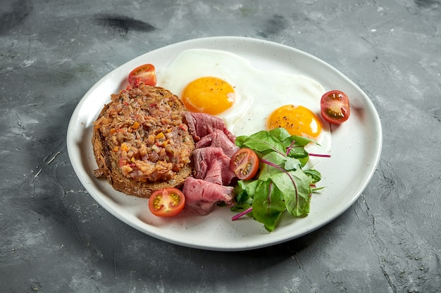 Appetizing breakfast - fried eggs with roast beef, tomatoes and salad, toast with stewed eggplant in a white plate on a gray surface