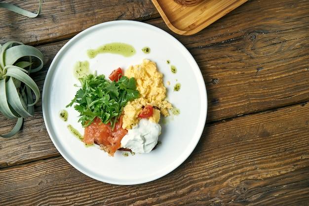 식욕을 돋 우는 아침 식사-나무에 접시에 그리스 요구르트와 arugula, 연어와 토스트와 스크램블 계란