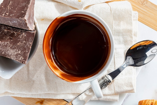 Appetizing breakfast with a delicious cup of thick, drinkable hot chocolate, along with chocolate bars.