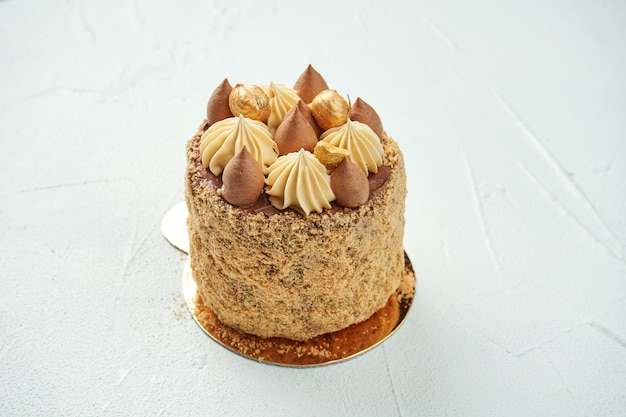 Appetizing brown cake with a velvet texture, white chocolate and caramel pear flavor on a white textured surface. stylish dessert pastries. kiev cake