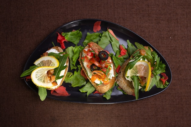 검정 잉크 판에 채소와 함께 식욕을 돋우는 bruschets. 요리사의 요리.