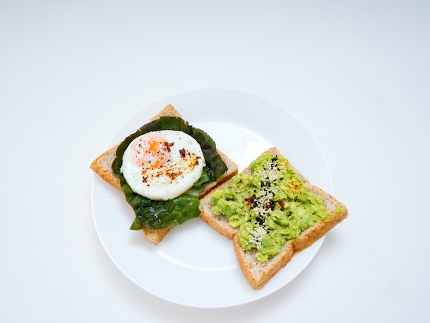 Appetizing bruschetta with egg and avocado on a plate. on the sandwich, the avocado pulp