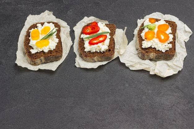Appetizing bruschetta with various toppings on paper. black background. top view. copy spacy