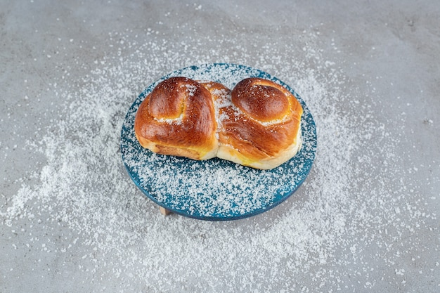 Appetizing bun on a blue stand on marble surface