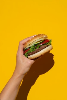 Appetizing burger in front of yellow background