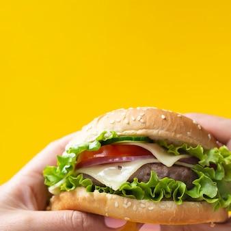 노란색 배경에 식욕을 돋 우는 햄버거 프리미엄 사진