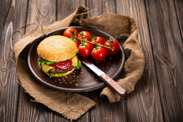 Appetizing burger with tomatoes on table