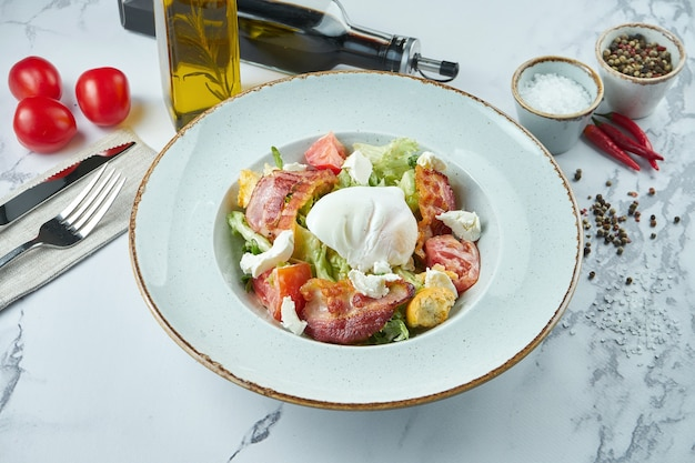 Appetizing caesar or lardon salad with croutons, bacon, feta cheese, tomatoes and poached egg in a blue plate on a marble surface