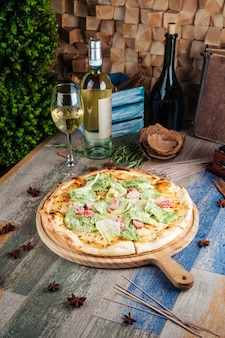 Appetizing caesar pizza with tomatoes and lettuce