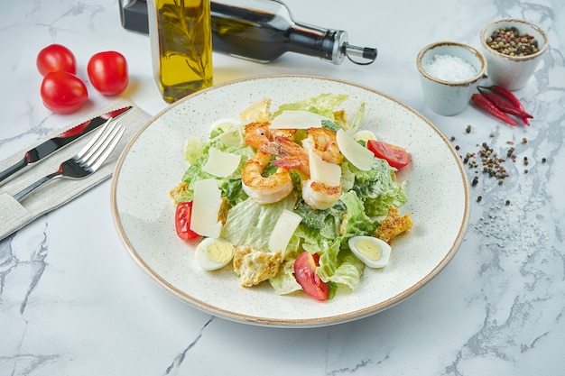 Appetizing caesar salad with shrimps, croutons, parmesan, tomatoes and anchovy sauce in a white plate on a marble surface