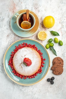 Torta appetitosa una tazza di tè con cannella e limone accanto al piatto di torta con fragole e semi di melograno biscotti al cioccolato sul tavolo